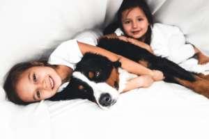 deux jeunes filles entrain de faire un câlin à un chien